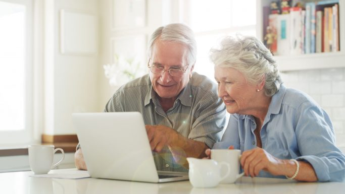 Seniorpar taler sammen foran PC